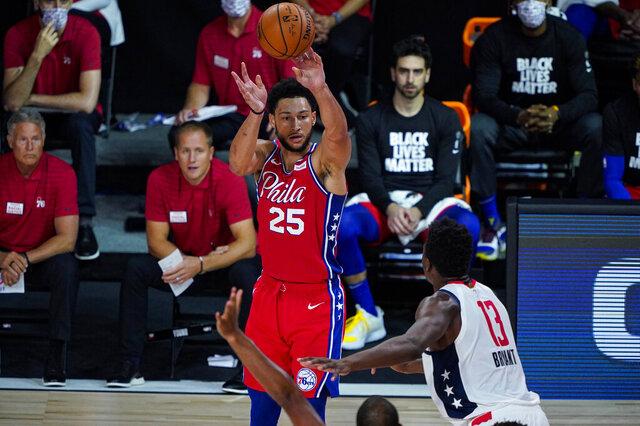 Philadelphia 76ers guard Ben Simmons (25) shoots over Washington Wizards center Thomas Bryant (13) during the second half of an NBA basketball game Wednesday, Aug. 5, 2020 in Lake Buena Vista, Fla. (AP Photo/Ashley Landis)