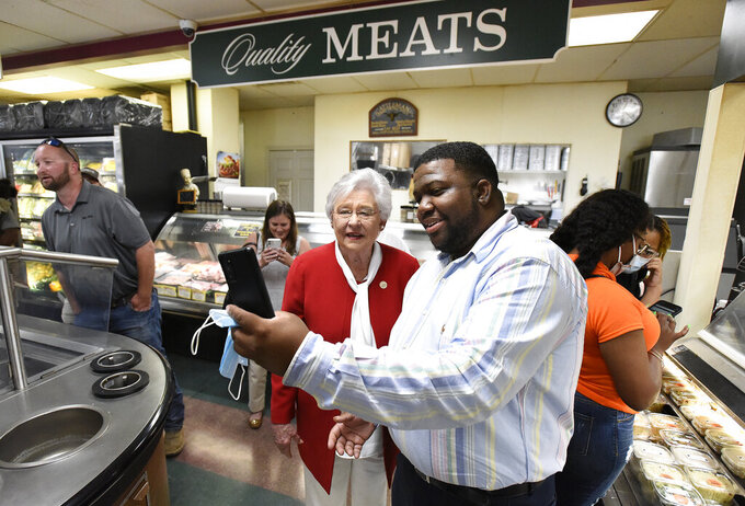 """Alabama Governor Kay Ivey takes a selfie with Lakeaton Pearson at Filet & Vine in Montgomery, Ala., as she makes her first campaign stop on Wednesday June 2, 2021. Ivey announced Wednesday that she's running for reelection, citing Alabama's """"bucket load of common sense"""" in its response to the coronavirus pandemic. Ivey, 76, made the announcement in a video message released by her campaign. (Mickey Welsh/The Montgomery Advertiser via AP)"""