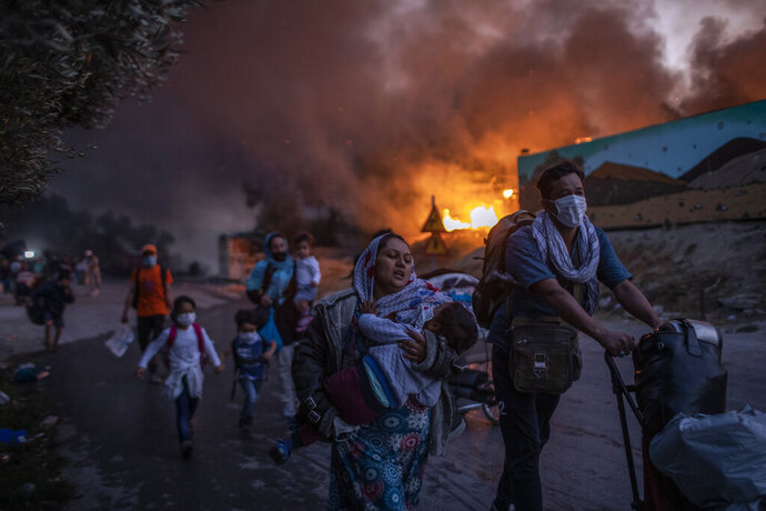 Refugees and migrants carrying their belongings flee a fire burning at the Moria camp on Lesbos island, Greece, Wednesday, Sept. 9, 2020. Moria refugee camp was never far from crisis. Created in the wake of a massive influx of migrants five years ago, Greece's largest refugee facility quickly exceeded capacity, spilling into surrounding olive groves on the island of Lesbos. The camp's life ended as it began, in drama: Successive fires that started before dawn on Sept. 9 devastating the site and making 12,000 inhabitants homeless during a COVD-19 lockdown. (AP Photo/Petros Giannakouris)