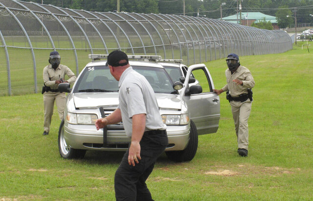 FILE - In this May 11, 2017 file photo, trainer Brad Drawdy runs away from two police officer trainees during an exercise  at the South Carolina Criminal Justice Academy in Columbia, S.C..  South Carolina lawmakers are looking to end a practice that allowed police officers in the state to patrol by themselves for up to a year without training. A bill receiving broad support in the South Carolina House would require an untrained officer to patrol with an officer who completed training at the state Criminal Justice Academy.  (AP Photo/Jeffrey Collins, File)