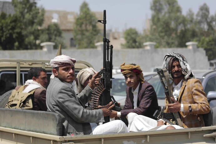"""FILE - In this Aug. 22, 2020 file photo, tribesmen loyal to Houthi rebels hold their weapons as they ride in a vehicle during a gathering against the agreement to establish diplomatic relations between Israel and the United Arab Emirates, in Sanaa, Yemen. Human Rights Watch warned Monday, Sept. 14, 2020 that warring parties in Yemen's yearslong conflict are """"severely restricting"""" the delivery of desperately needed aid as the country slides toward famine amid the coronavirus pandemic. (AP Photo/Hani Mohammed, File)"""