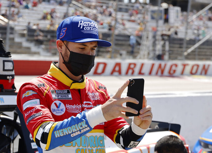 FILE - In this Sunday, May 9, 2021, file photo, Kyle Larson uses his cell phone before the NASCAR Cup Series auto race at Darlington Raceway in Darlington, S.C. Larson took time out from his NASCAR schedule to Zoom in with the class at Philadelphia's Urban Youth Racing School. The Philly-based program that creates opportunities in racing for minorities extended an olive branch last year to Larson after the driver was caught using a slur during an iRacing event in April.(AP Photo/Terry Renna, File)