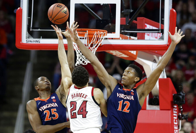 Virginia's Mamadi Diakite (25) and De'Andre Hunter defend against North Carolina State's Devon Daniels (24) during the second half of an NCAA college basketball game in Raleigh, N.C., Tuesday, Jan. 29, 2019. Virginia won 66-65 in overtime. (AP Photo/Gerry Broome)