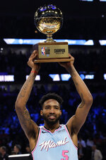 Miami Heat's Derrick Jones Jr. holds the trophy after he won the NBA All-Star slam dunk contest in Chicago, Saturday, Feb. 15, 2020. (AP Photo/Nam Y. Huh)