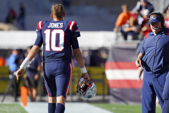 New England Patriots quarterback Mac Jones (10) walks off the field past head coach Bill Belichick late in the second half of an NFL football game against the New Orleans Saints, Sunday, Sept. 26, 2021, in Foxborough, Mass. (AP Photo/Mary Schwalm)