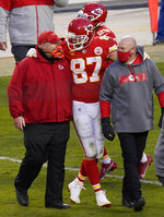 FILE - In this Jan. 17, 2021, file photo, Kansas City Chiefs tight end Travis Kelce (87) walks off the field with coach Andy Reid after an NFL divisional round football game against the Cleveland Browns in Kansas City, Mo. Both Reid and Bruce Arians are considered players' coaches, though they do it in different ways. It's a quality that's helped them reach the Super Bowl. (AP Photo/Orlin Wagner, File)