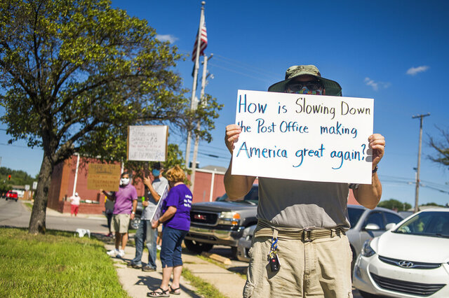 Eric Severson holds a sign as a few dozen people gather in front of the United States Post Office on Rodd St. to protest recent changes to the U.S. Postal Service under new Postmaster General Louis DeJoy Tuesday, Aug. 11, 2020 in Midland, Mich. (Katy Kildee/Midland Daily News via AP)