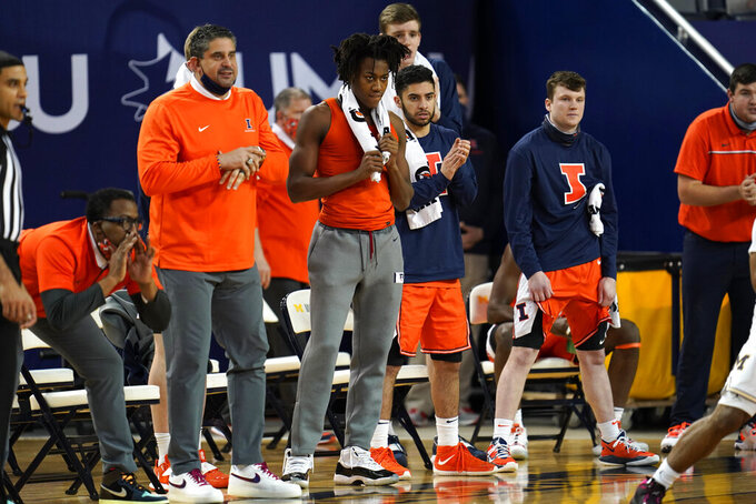 Illinois guard Ayo Dosunmu watches from the bench in sweats and a towel around his neck in the first half of an NCAA college basketball game against Michigan in Ann Arbor, Mich., Tuesday, March 2, 2021. Dosunmu did not play. (AP Photo/Paul Sancya)