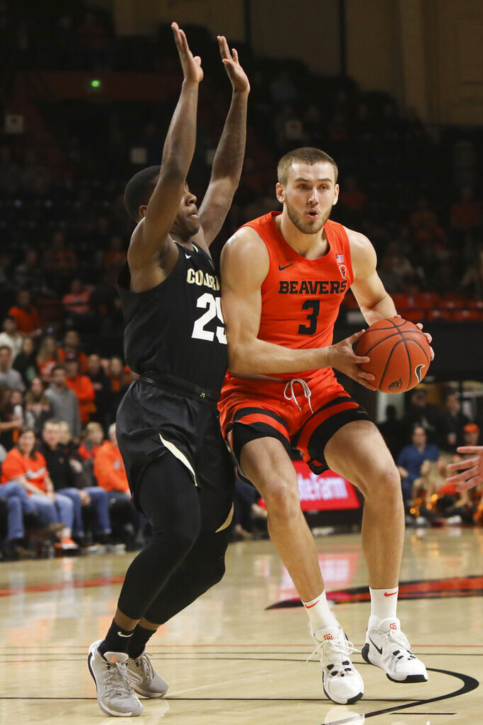 Oregon State's Tres Tinkle (3) runs up against Colorado's McKinley Wright IV (25) during the first half of an NCAA college basketball game in Corvallis, Ore., Saturday, Feb. 15, 2020. (AP Photo/Amanda Loman)