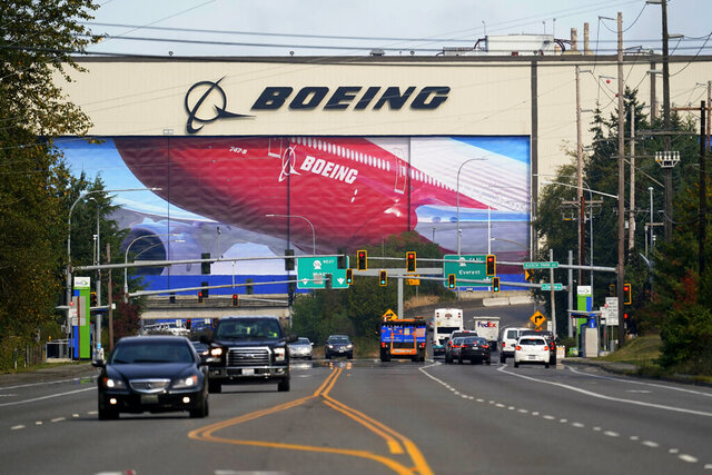 Traffic passes in view of a massive Boeing airplane production plant Thursday, Oct. 1, 2020, in Everett, Wash. Boeing said Thursday that it will consolidate production of its two-aisle 787 jetliner in South Carolina and shut down the original assembly line for the plane near Seattle. The company said the move will start in mid-2021. (AP Photo/Elaine Thompson)