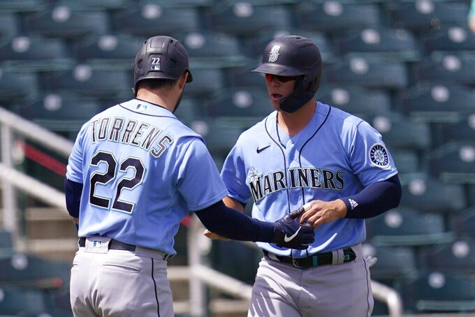 Seattle Mariners' Ty France, right, celebrates his run scored against the Cincinnati Reds with teammate Luis Torrens, left,  during the first inning of a spring training baseball game Monday, March 29, 2021, in Goodyear, Ariz. (AP Photo/Ross D. Franklin)