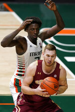 Miami center Nysier Brooks, rear, blocks the path of Boston College forward James Karnik during the second half of an NCAA college basketball game Friday, March 5, 2021, in Coral Gables, Fla. (AP Photo/Wilfredo Lee)