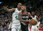 Portland Trail Blazers guard Damian Lillard (0) drives past Boston Celtics center Al Horford (42) during the second half of an NBA basketball game Wednesday, Feb. 27, 2019, in Boston. (AP Photo/Mary Schwalm)