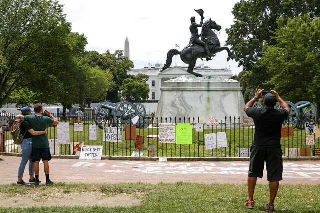 People visit Lafayette Park where protest signs are seen along the fencing that surrounds a statue of President Andrew Jackson, Tuesday, June 16, 2020, near the White House in Washington, where protests have occurred over the death of George Floyd, a black man who was in police custody in Minneapolis. (AP Photo/Jacquelyn Martin)