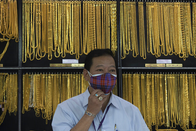 FILE - In this April 16, 2020, file photo, a Thai shopkeeper adjusts his face mask at a gold shop in Bangkok, Thailand. The price of gold surged more than $30 on Monday, July 27, 2020 to over $1,926 per ounce as investors step up buying of the precious metal often sought in times of uncertainty. Gold was trading at $1,926.20 by early afternoon in Asia, up 1.5%, after surging over the weekend. (AP Photo/Sakchai Lalit, File)