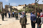 Policemen and civilians stand in front of damaged buildings in the town of Douma, the site of a suspected chemical weapons attack, near Damascus, Syria, Monday, April 16, 2018. Faisal Mekdad, Syria's deputy foreign minister, said on Monday that his country is