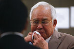 Former Malaysia Prime Minister Najib Razak, centre, wipes his sweat before leaving the Kuala Lumpur High Court complex in Kuala Lumpur, Malaysia, Tuesday, July 28, 2020. The court has sentenced Razak to serve 12 years in prison after finding him guilty in the first of several corruption trials linked to the multibillion-dollar looting of a state investment fund that brought down his government two years ago. (Fazry Ismail/Pool Photo via AP)