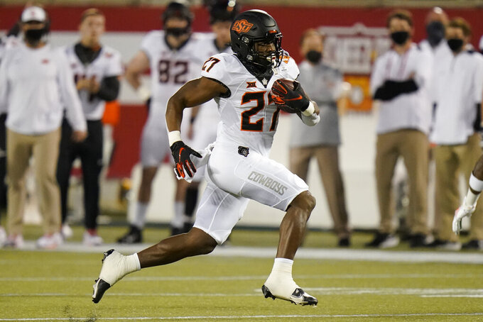 FILE - Oklahoma State running back Dezmon Jackson gains yardage against Miami during the first half of the Cheez-it Bowl NCAA college football game in Orlando, Fla., in this Tuesday, Dec. 29, 2020, in file photo. LD Brown, Dezmon Jackson, Dominic Richardson and Jaylen Warren will share the load for the Cowboys this season. None has been designated as the clear starter heading into next Saturday's opener against Missouri State, something coach Mike Gundy considers a good thing. (AP Photo/John Raoux, File)