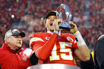In this Jan. 19, 2020, photo, Kansas City Chiefs quarterback Patrick Mahomes holds the Lamar Hunt Trophy as he celebrates winning a NFL, AFC Championship football game against the Tennessee Titans in Kansas City, Mo. The most compelling dramas in the NFL this season unfolded on the field, not off of it. And any thought that the league was in jeopardy of losing its spot as America's favorite sport has been set on the back burner. (AP Photo/Colin E. Braley)