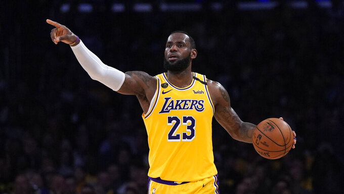 FILE - In this March 6, 2020, file photo, Los Angeles Lakers forward LeBron James gestures to teammates during the second half of an NBA basketball game against the Milwaukee Bucks in Los Angeles.  James was announced Saturday, Dec. 26,  as the winner of The Associated Press' Male Athlete of the Year award for a record-tying fourth time.(AP Photo/Mark J. Terrill, File)