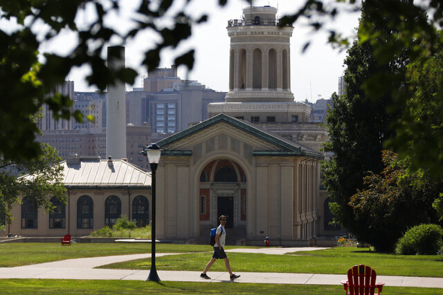 FILE - In this file photo from June 7, 2019, a man walks by Hamerschlag Hall on the Carnegie Mellon University campus in Pittsburgh. Colleges in the U.S. have seen a sharp enrollment drop among international students in the fall of 2020. University administrators say a number of hurdles and new policies brought on by the coronavirus pandemic are to blame. (AP Photo/Gene J. Puskar, File)