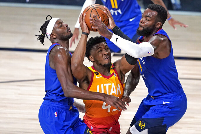 FILE - In this Aug. 30, 2020, file photo, Utah Jazz's Donovan Mitchell, center, goes up to shoot as Denver Nuggets' Jerami Grant, left, and Paul Millsap, right, defend during the second half of an NBA basketball first round playoff game in Lake Buena Vista, Fla. Mitchell agreed Sunday, Nov. 22, 2020, to a five-year, $163 million extension to remain with the Jazz. (AP Photo/Ashley Landis, File)