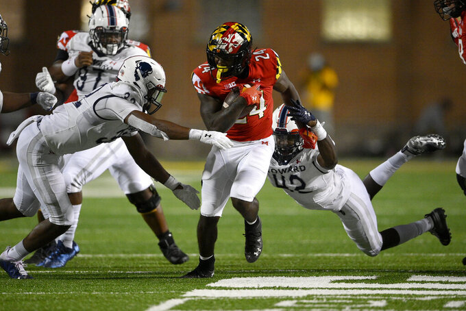 Maryland running back Roman Hemby, center, runs with the ball against Howard defensive lineman Marcus Brown (42) and linebacker Terrence Hollon, front left, during the second half of an NCAA college football game, Saturday, Sept. 11, 2021, in College Park, Md. (AP Photo/Nick Wass)
