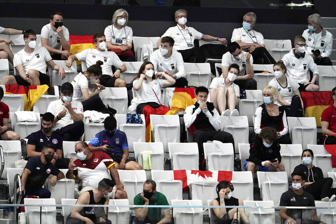 Athletes and staff members watch the women's synchronized 3-meter springboard preliminary at the FINA Diving World Cup Saturday, May 1, 2021, at the Tokyo Aquatics Centre in Tokyo. (AP Photo/Eugene Hoshiko)