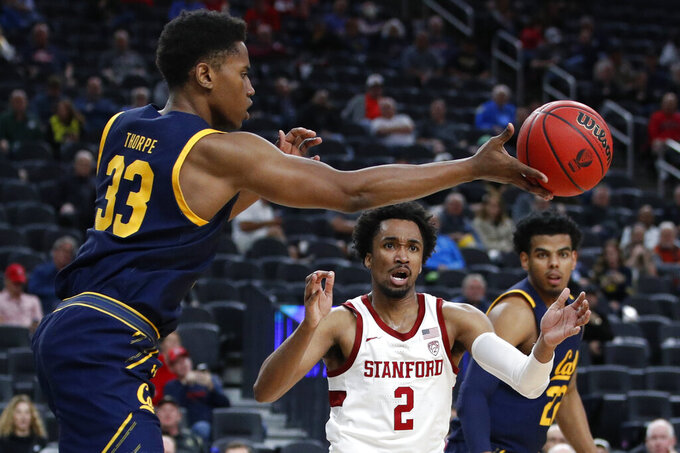 California's D.J. Thorpe (33) passes around Stanford's Bryce Wills (2) during the second half of an NCAA college basketball game in the first round of the Pac-12 men's tournament Wednesday, March 11, 2020, in Las Vegas. (AP Photo/John Locher)