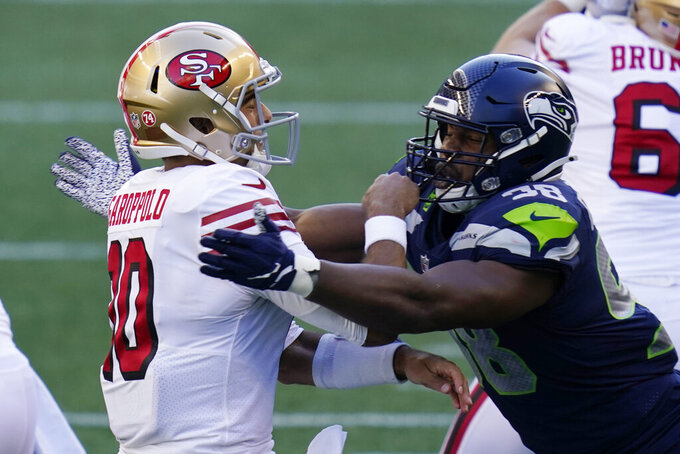 Seattle Seahawks' defensive end Alton Robinson, right, pressures San Francisco 49ers quarterback Jimmy Garoppolo, left, after Garoppolo got a pass off during the first half of an NFL football game, Sunday, Nov. 1, 2020, in Seattle. (AP Photo/Elaine Thompson)
