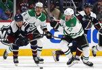 Colorado Avalanche right wing Mikko Rantanen, left, and Dallas Stars center Mattias Janmark, right, pursue the puck as defenseman Andrej Sekera trails the play in the second period of an NHL hockey game Tuesday, Jan. 14, 2020, in Denver. (AP Photo/David Zalubowski)