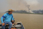 Daniel Moura, an eco-tourism guide, rides his boat on the Cuiaba river as fires burn in the Encontro das Aguas Park near Pocone, Mato Grosso state, Brazil, Saturday, Sept. 12, 2020. The Pantanal, the world's largest tropical wetlands and a biodiversity hot spot, this year is exceptionally dry and burning at a record rate. (AP Photo/Andre Penner)