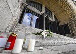 Flowers and candles are set in front of the old synagogue in Essen, Germany, Thursday, Oct. 10, 2019. A heavily armed assailant ranting about Jews tried to force his way into a synagogue in Halle, Germany yesterday, before he killed two people nearby. (AP Photo/Martin Meissner)