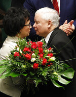 Leader of Poland's ruling right-wing party, Jaroslaw Kaczynski, right, offers flowers to his party member Elzbieta Witek, after she was chosen AS the speaker of the new lower house of parliament after elections, at its inaugural session in Warsaw, Poland, Tuesday, Nov. 12, 2019.(AP Photo/Czarek Sokolowski)