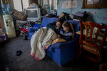 A woman rests with her daughter inside their home at the Canada Real shanty town, outside Madrid, Spain, Tuesday, Jan. 12, 2021.  Shops are flimsy set-ups with little stock and the residents live off construction jobs, scrap metal collection or whatever they can, and the area has long been associated with drugs. (AP Photo/Manu Fernandez)