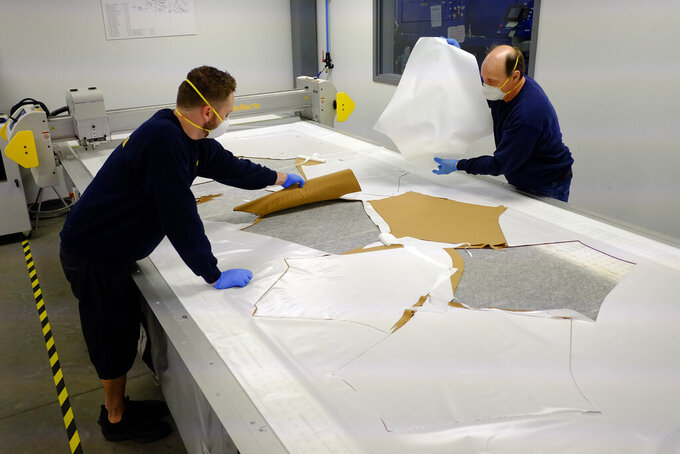 Dallara USA employees Michael Carlisle, left, and Marty Bigley cut out material patterns for protective medical gowns during the coronavirus pandemic, Wednesday, April 15, 2020, in Indianapolis. (AP Photo/Darron Cummings)