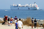 Local residents watch as the USNS Comfort departs Hampton Roads en route to New York to help in the response to the coronavirus outbreak Saturday, March 28, 2020, in Hampton, Va. (AP Photo/Steve Helber)