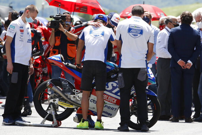 Teammates of 19 years-old Swiss pilot Jason Dupasquier stand near his motorbike as they pay a minute of silence in his memory prior to the start of the Motogp Grand Prix of Italy at the Mugello circuit, in Scarperia, Italy, Sunday, May 30, 2021. Dupasquier died Sunday after being hospitalized Saturday, at the Florence hospital following his crash during the qualifying practices of the Moto3. (AP Photo/Antonio Calanni)