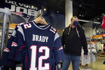 FILE - Football fan Brian Pope browses for Tom Brady jerseys in the pro shop at Gillette Stadium in Foxborough, Mass., in this Monday, Jan. 25, 2021, file photo. Brady's No. 12 Patriots jerseys are still plentiful in the stands on game days at Gillette Stadium. With Brady's new Tampa home just as rabid about the player who brought it a championship in Year 1, it's created a tug-of-war between the fan bases as he gets set to return to the place where his career began. (AP Photo/Elise Amendola, File)