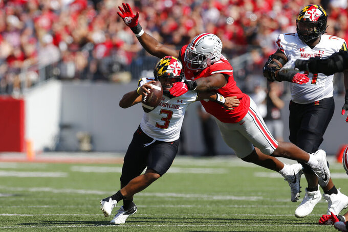 Ohio State defensive lineman Zach Harrison, right, tackles Maryland quarterback Taulia Tagovailoa during the first half of an NCAA college football game Saturday, Oct. 9, 2021, in Columbus, Ohio. (AP Photo/Jay LaPrete)