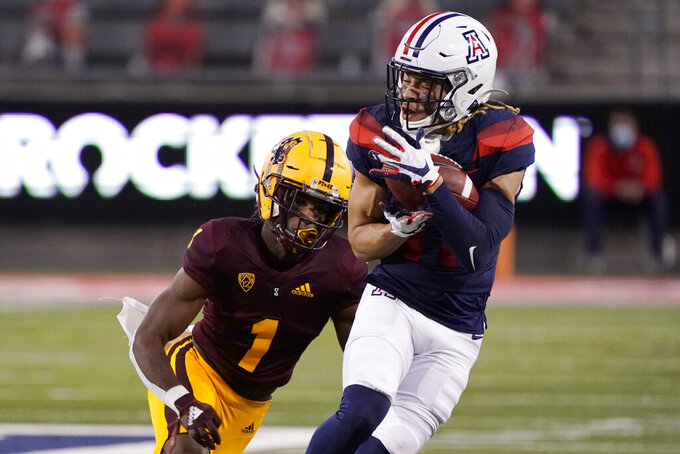 Arizona wide receiver Tayvian Cunningham makes a catch in front of Arizona State defensive back Jordan Clark (1) during the first half of an NCAA college football game Friday, Dec. 11, 2020, in Tucson, Ariz. (AP Photo/Rick Scuteri)