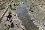 FILE - In this March 21, 2013, file photo, Arizona Diamondbacks minor league players walk along a stream between fields prior to a spring training baseball game against the Cleveland Indians, in Scottsdale, Ariz. With Major League Baseball successfully resisting legal efforts to raise minor league salaries, players are beginning to look elsewhere to make ends meet. (AP Photo/Matt York, File)
