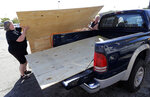 Mickey Manes, right, and Diane Manes, left, load plywood into their truck in advance of Hurricane Florence in Wilmington, N.C., Wednesday, Sept. 12, 2018. Florence exploded into a potentially catastrophic hurricane Monday as it closed in on North and South Carolina, carrying winds up to 140 mph (220 kph) and water that could wreak havoc over a wide stretch of the eastern United States later this week. (AP Photo/Chuck Burton)
