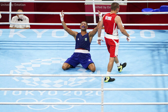Brazil's Hebert Sousa, left, celebrates winning his men's middleweight 75-kg boxing gold medal match against Ukraine's Oleksandr Khyzhniak at the 2020 Summer Olympics, Saturday, Aug. 7, 2021, in Tokyo, Japan. (AP Photo/Frank Franklin II)