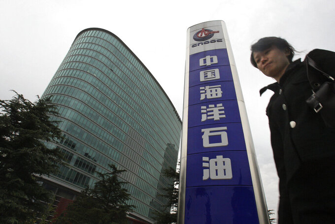 FILE - In this Oct. 29, 2008, file photo, a woman walks past the headquarters of the state-owned China National Offshore Oil Corp. CNOOC, in Beijing. U.S. President Joe Biden has nearly doubled the list of Chinese companies whose shares are off-limits to U.S. investors in the latest sign he is not softening Washington's stance toward Beijing. Telecoms equipment maker Huawei Technologies, China's big state-owned telecoms companies and China National Offshore Oil Corp. are on the new list of 59 companies. (AP Photo/Ng Han Guan, File)