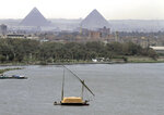 """FILE - In this file photo of Tuesday, Jan. 22, 2013, a traditional felucca sailing boat carries a cargo of hay as it transits the Nile river passing the Pyramids of Giza in Cairo, Egypt, Irrigation ministers from three key Nile Basin countries wrapped up a two-day meeting Saturday in Sudan's capital without agreeing on differences over Ethiopia's soon-to-be-finished Blue Nile dam, with Egypt calling for international mediation to help reach a """"fair and balanced"""" agreement. (AP Photo/Amr Nabil-File)"""