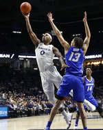 Xavier's Tyrique Jones (0) shoots next to Creighton's Christian Bishop (13) during the first half of an NCAA college basketball game Wednesday, Feb. 13, 2019, in Cincinnati. (AP Photo/John Minchillo)