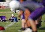 In this Aug. 5, 2019,  photo, Tom Ramsay sits along the sideline and watches the team's first practice lead by new head coach Art Briles at Mount Vernon High School in Mount Vernon, Texas. (AP Photo/Tony Gutierrez)
