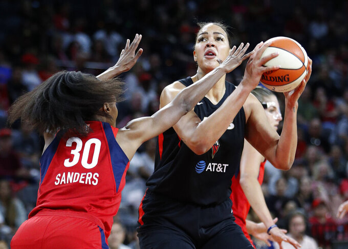FILE - In this Tuesday, Sept. 24, 2019, file photo, Las Vegas Aces' Liz Cambage shoots against Washington Mystics' LaToya Sanders during the first half of Game 4 of a WNBA playoff basketball series in Las Vegas. All-Star center Cambage is expected to miss the upcoming 2020 WNBA season for health reasons, according to her agent. (AP Photo/John Locher, File)
