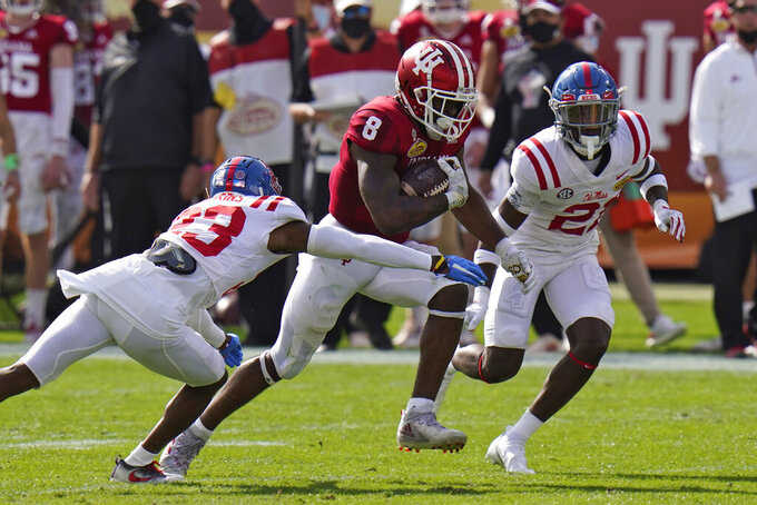 Indiana running back Stevie Scott III (8) slips between Mississippi defensive back Jakorey Hawkins (23) and defensive back A.J. Finley (21) during the first half of the Outback Bowl NCAA college football game Saturday, Jan. 2, 2021, in Tampa, Fla. (AP Photo/Chris O'Meara)